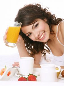 woman smiling drinking orange juice
