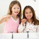 Two Young Girls Brushing Teeth at Sink