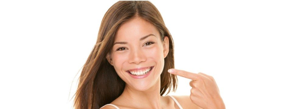 young woman smiling and pointing at teeth